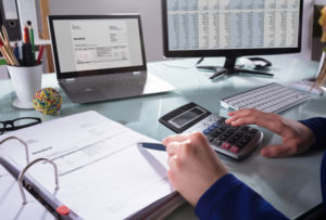 Man bookkeeping at a desk with a calculator book and computer