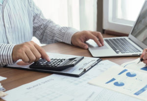 Accountant at computer also working with a calculator